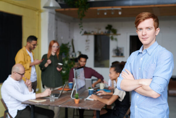 Young entrepreneur smiling with his team in background